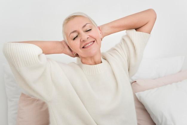 Vista frontal de sonriente anciana estiramiento