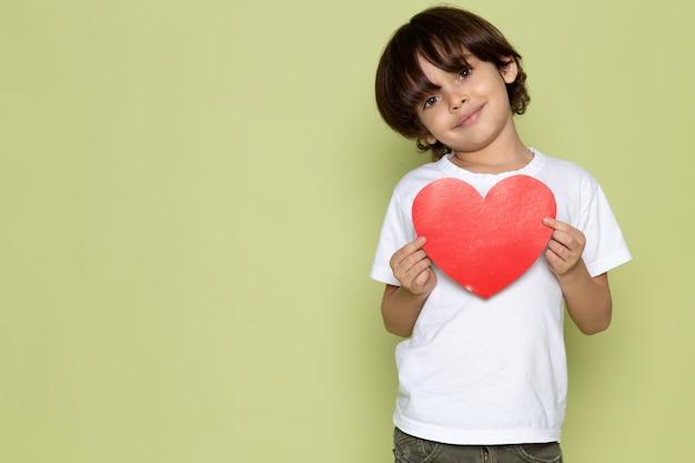 Una vista frontal sonriente chico lindo en camiseta blanca y con forma de corazón en el espacio de color piedra