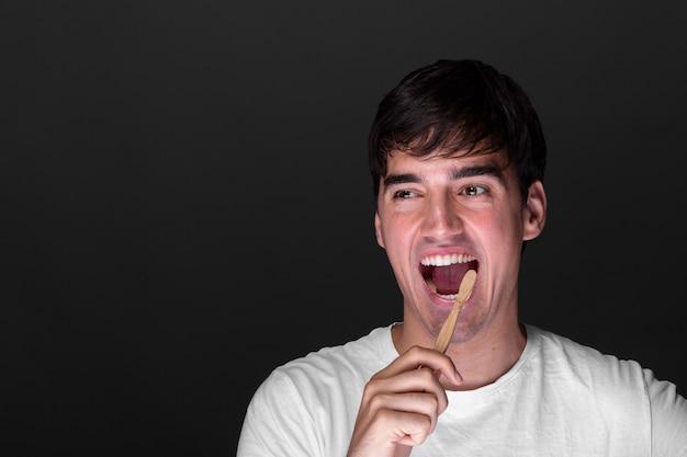 Vista frontal sonriente hombre cepillarse los dientes