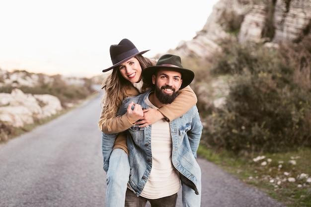 Vista frontal sonriente hombre y mujer en una carretera de montaña