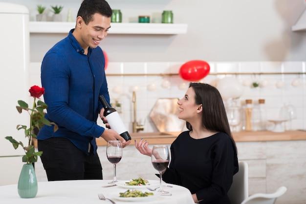 Vista frontal sonriente hombre vertiendo vino en un vaso para su esposa