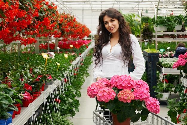 Vista frontal de la sonriente joven morena atractiva en camiseta blanca de pie con carro y elegir hermosas flores. concepto de proceso de venta de macetas con flores increíbles.