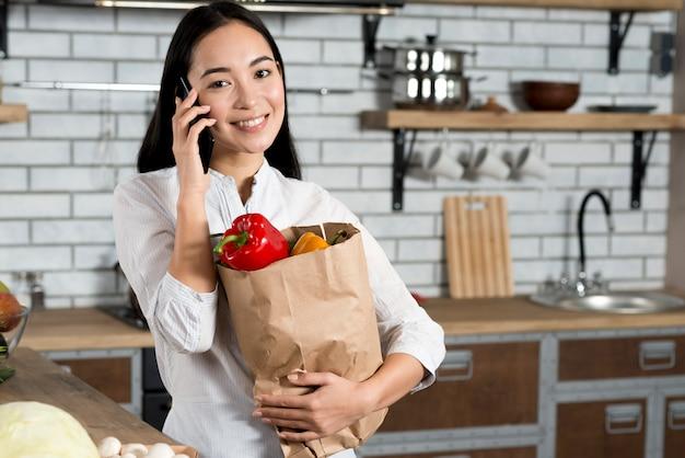 Vista frontal de la sonriente mujer asiática hablando por teléfono móvil mientras sostiene la bolsa de la compra