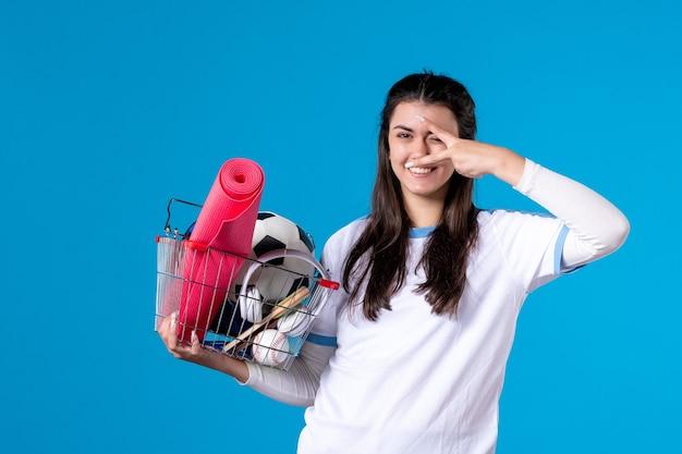 Vista frontal sonriente mujer joven con canasta después de compras deportivas