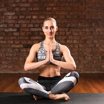 Vista frontal sonriente mujer meditando