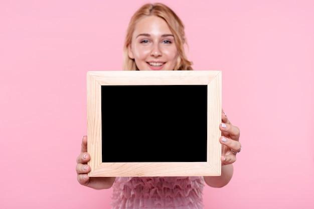 Vista frontal sonriente mujer mostrando marcos