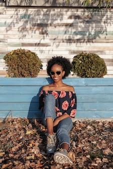 Vista frontal sonriente mujer de pelo rizado con gafas de sol