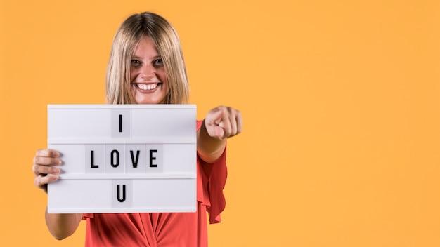 Vista frontal sonriente mujer sosteniendo caja de luz con te amo texto contra superficie amarilla