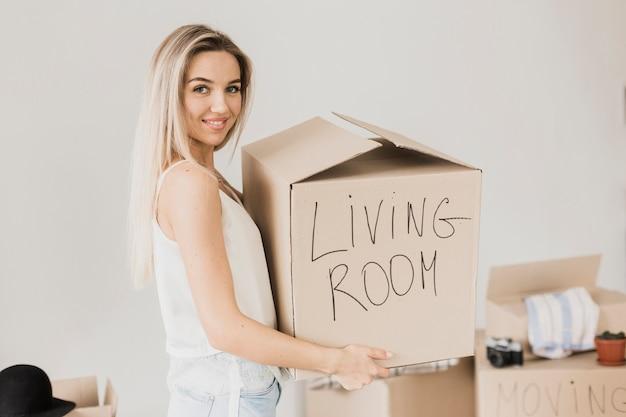 Vista frontal sonriente mujer sosteniendo caja