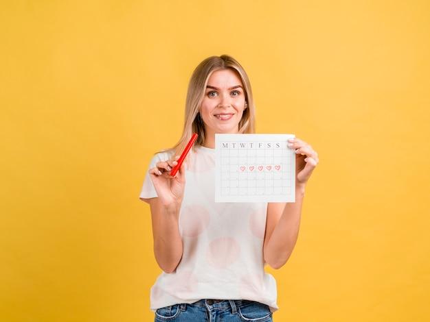 Vista frontal sonriente mujer sosteniendo calendario período