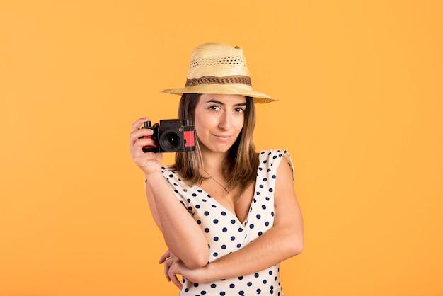 Vista frontal sonriente mujer sosteniendo la cámara