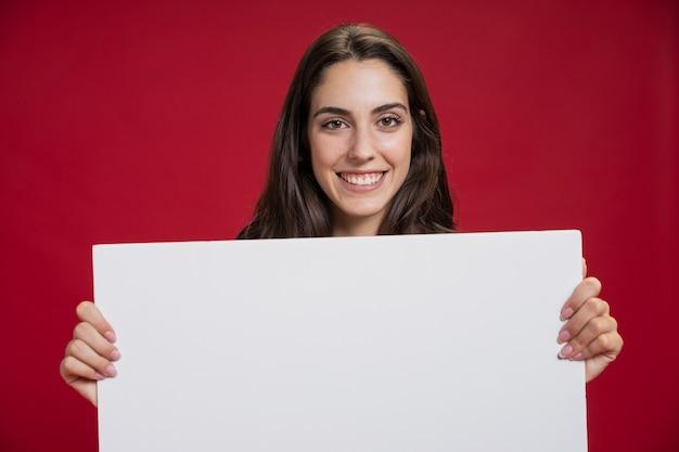 Vista frontal sonriente mujer sosteniendo una pancarta vacía