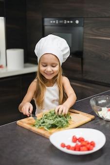 Vista frontal de sonriente niña cortando vegetales en tabla de cortar de madera