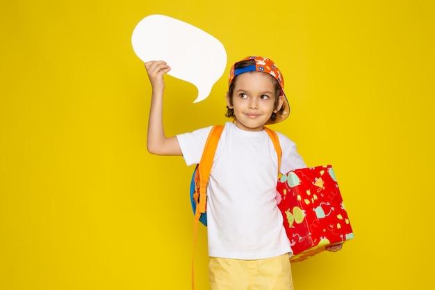 Vista frontal sonriente niño lindo en camiseta blanca y gorra de béisbol sobre piso amarillo