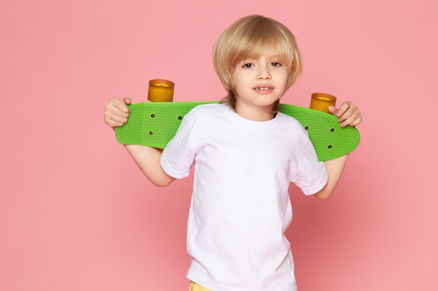 Una vista frontal sonriente niño rubio en camiseta blanca con patineta verde en el espacio rosa
