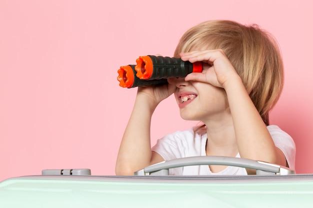 Vista frontal, sonriente, niño, rubio, pelo, usar binoculares, en, rosa