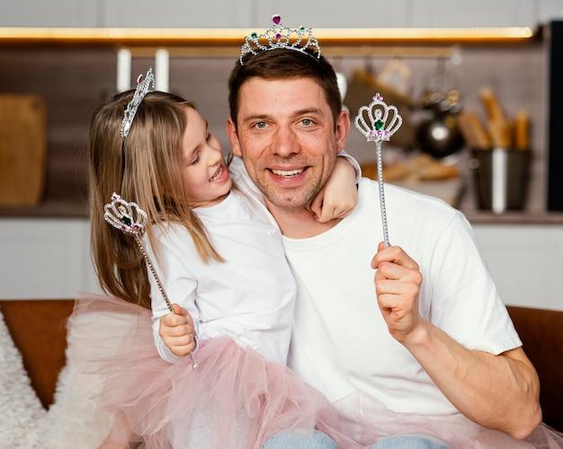 Vista frontal de sonriente padre e hija jugando con tiara y varita