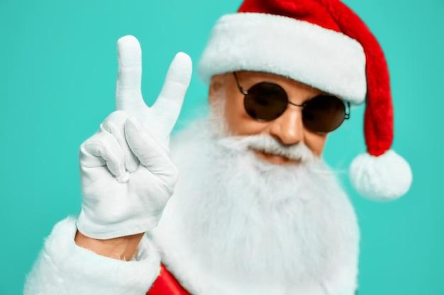 Vista frontal del sonriente papá noel con larga barba blanca que muestra la paz con dos dedos hacia arriba