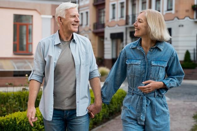 Vista frontal de la sonriente pareja de ancianos en la ciudad