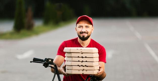Vista frontal sonriente repartidor sosteniendo cajas de pizza
