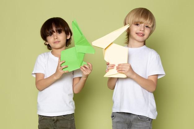 Una vista frontal sonrientes muchachos en camisetas blancas con juguetes de papel en la pared de color piedra