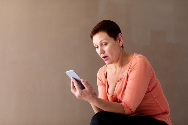 Vista frontal sorprendida mujer con teléfono