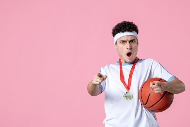 Vista frontal sorprendido jugador de baloncesto sosteniendo la bola con medalla