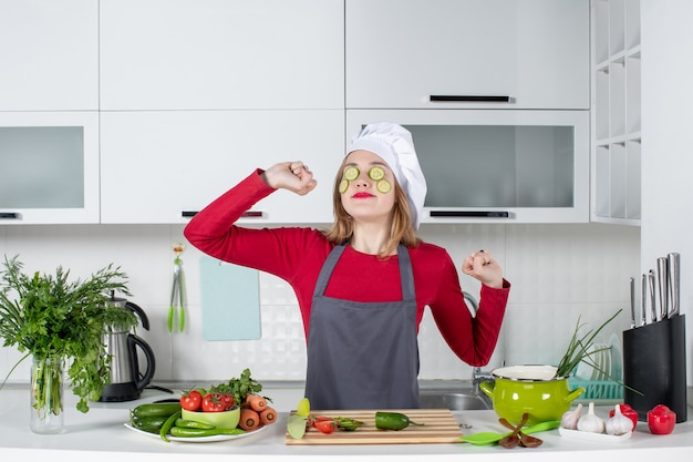 Vista frontal streching chef femenina en uniforme poniendo rodajas de pepino en su cara