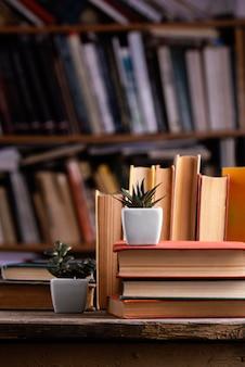 Vista frontal de suculentas y libros de tapa dura en la biblioteca.