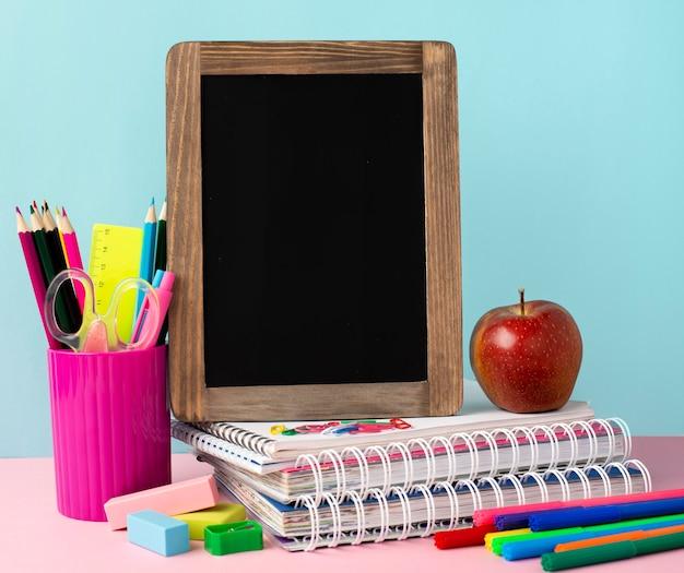 Vista frontal de suministros de regreso a la escuela con cuadernos y manzana