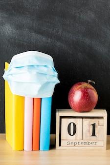 Vista frontal de suministros de regreso a la escuela con máscara médica y libros