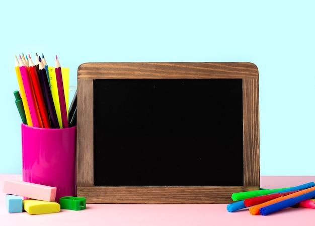 Vista frontal de suministros de regreso a la escuela con pizarra y lápices