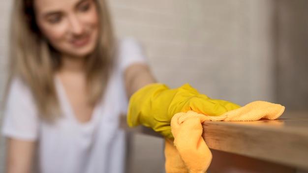 Vista frontal de la superficie de limpieza de mujer desenfocada