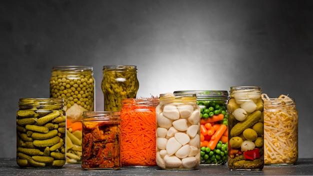 Vista frontal del surtido de verduras encurtidas en frascos de vidrio