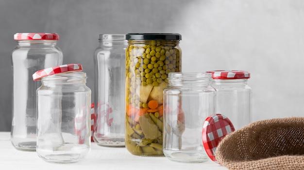 Vista frontal del surtido de verduras en escabeche en frasco de vidrio