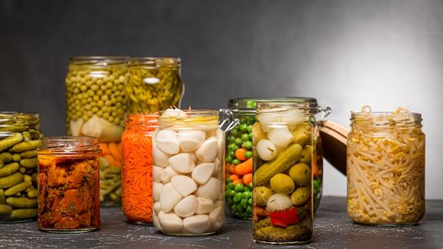 Vista frontal del surtido de verduras en escabeche en frascos de vidrio transparente