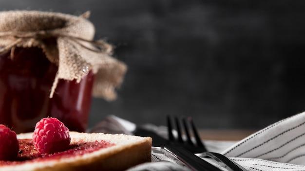 Vista frontal del tarro de mermelada con frambuesas y pan