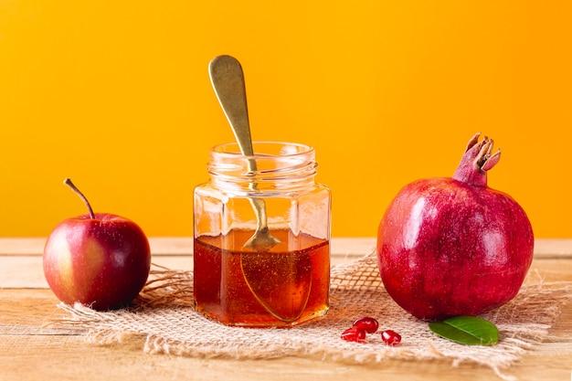 Vista frontal tarro de miel con cuchara y frutas