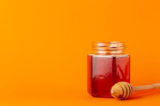 Vista frontal tarro de miel y cucharón con espacio de copia