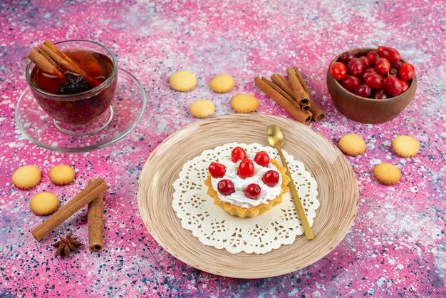 Vista frontal de la tarta con crema fresca y frutas frescas junto con canela y una taza de té en el dulce pastel de escritorio brillante