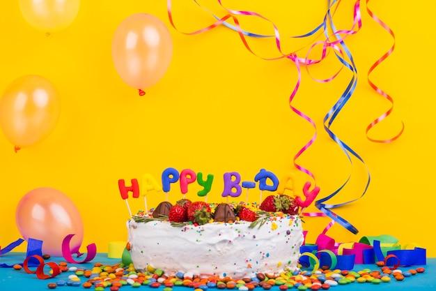 Vista frontal tarta cumpleaños rodeada de elementos de fiesta
