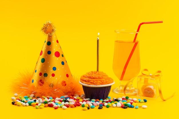 Vista frontal de una tarta de cumpleaños con velas junto con caramelos de colores y gorro de cumpleaños en color amarillo, galleta dulce