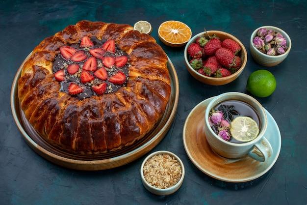 Vista frontal de la tarta de fresa con una taza de té en la superficie azul oscuro