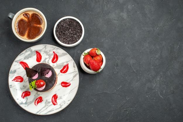 Vista frontal de tarta de queso de fresa en cuencos de placa ovalada blanca con fresas y chocolate una taza de café sobre fondo oscuro espacio libre