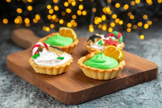 Vista frontal de tartas pequeñas en una tabla de cortar en luces de navidad de superficie oscura