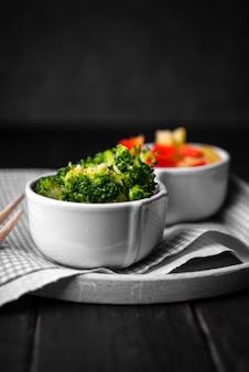 Vista frontal de la taza de brócoli en plato con tela