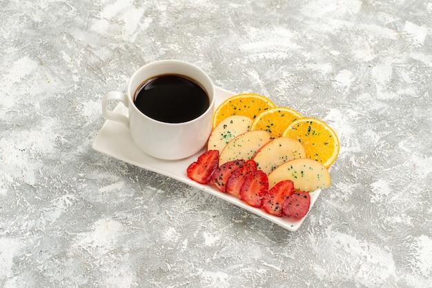 Vista frontal de la taza de café con rodajas de manzanas, naranjas y fresas sobre un fondo blanco claro frutas maduras suaves frescas