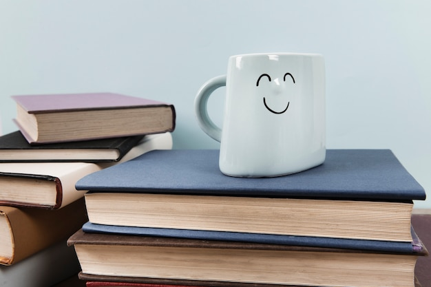 Vista frontal de la taza feliz en libros con fondo liso
