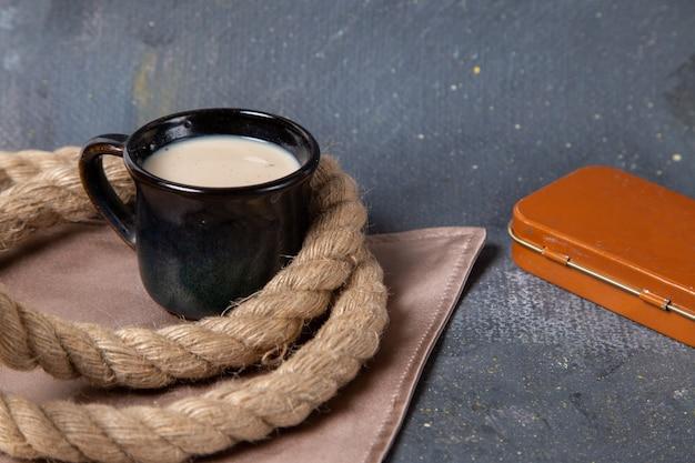 Vista frontal de la taza de leche con cuerdas en la superficie gris
