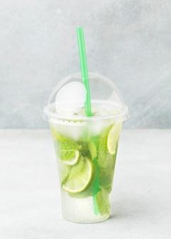 Vista frontal de la taza con refresco y limón.